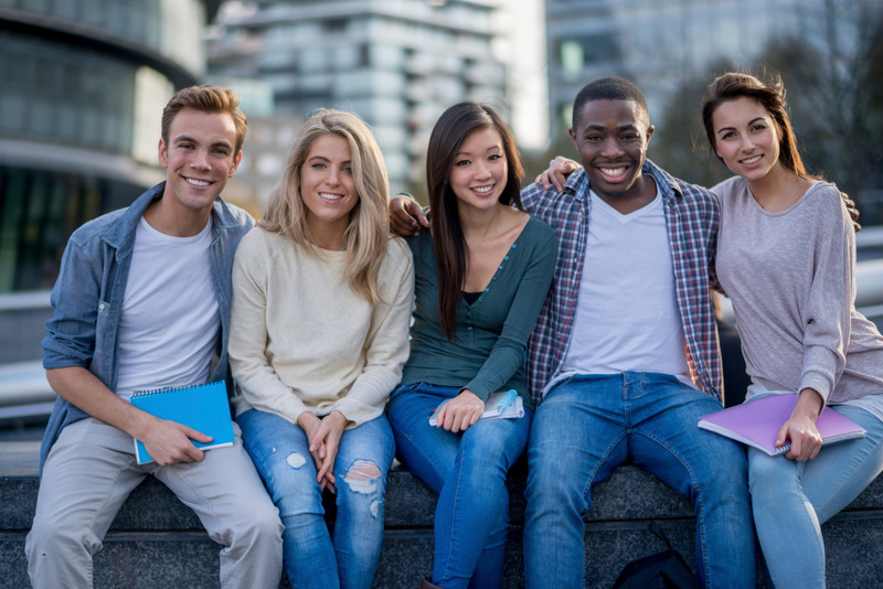 5 young people sitting and smiling